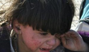 A Syrian child cries during the UN-led evacuation of thousands of civilians from the besieged city of Homs, on February 12, 2014