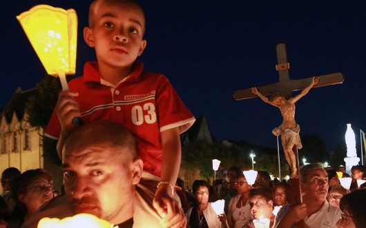 Pilgrims attend a candlelight procession on the eve of Assumption Foto AP Photo oleh Bob Edme