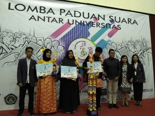 Para pemenang Lomba Paduan Suara Antar Universitas di GOR UNITRI, menerima piala dan uang dari dewan juri