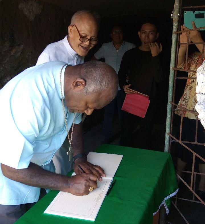 Ditemani Pastor Jacobus Wagey Pr, John Kardinal Ribat dari Papua New Guina mengunjungi dan menandatangani daftar orang yang mengunjungi Gua Maria di Lotta