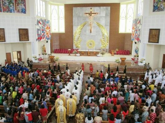 Perarakan uskup dan para imam diiringi tarian khas Dayak Kalbar