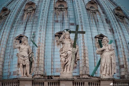 Yesus Kristus berdiri di antara Santo Yohanes Pembaptis dan Santo Andreas di depan kuba Basilika Santo Petrus. Foto oleh Lisa Johnston
