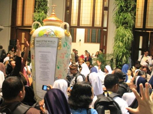 """300 kaum religius Indonesia yang mengikuti Penutupan Tahun Hidup Bakti di Lembang, Jawa Barat, 2-5 Desember 2015, memberikan tanda telapak tangan pada bejana yang bertuliskan janji mereka untuk """"senantiasa melanjutkan peziarahan iman yang telah dimulai oleh para pendahulu dengan menyegarkan dan menghidupi spiritualitas dan karisma tarekat masing-masing."""""""