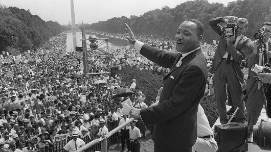 "Martin Luther King melambaikan tangan kepada pendukung dalam  ""March on Washington"" tahun 1963"