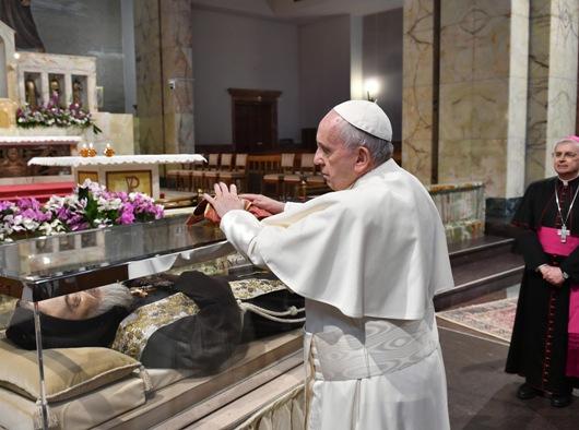 Paus Fransiskus meletakkan stola di kotak kaca yang berisi tubuh Santo Pio di Gereja Santa Maria delle Grazie di Tempat Ziarah Santo Pio dari  Pietrelcina di San Giovanni Rotondo, Italia, 17 Maret (CNS photo/courtesy Shrine of St. Pio of Pietrelcina)