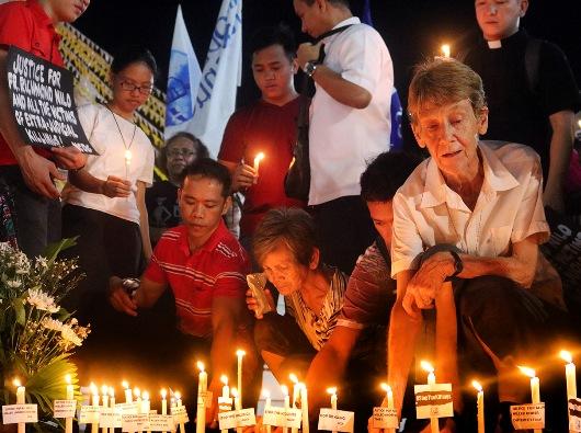 Suster Patricia Fox menyalakan lilin dalam doa untuk para imam Katolik yang terbunuh. Peristiwa ini berlangsung di luar Gereja Quiapo, Manila, 18 Juni 2018. RICHARD DE LEON