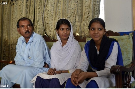 Suami dari Asia Bibi duduk bersama dua anak perempuannya