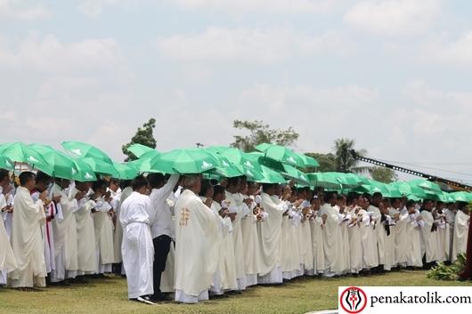 Para pastor ditemani prodiakon dan putra altar  siap membagikan komuni