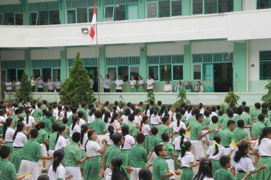 Para murid dan guru menari menyambut para tamu