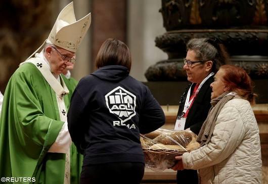 Paus Fransiskus menerima persembahan roti saat dia memimpin Misa khusus untuk merayakan Hari Orang Miskin se-Dunia yang pertama di Basilika Santo Petrus di Vatikan, 19 November 2017 - REUTERS