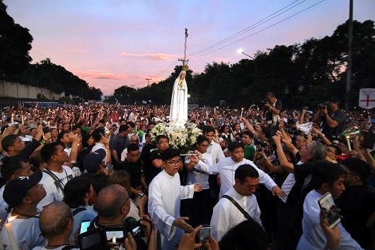 Orang-orang mengangkat lilin bernyalah saat menyambut patung Bunda Kita dari Fatima setelah prosesi untuk penyembuhan nasional dari Tempat Ziarah Edsa ke Monumen People Power di Quezon, 5 November 2017. ROY LAGARDE