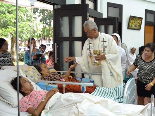Mgr Pius Riana Prapdi menerimakan Komuni kepada orang sakit
