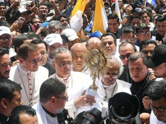 Kardinal Leopoldo Brenes memegang Sakramen Mahakudus di tengah kerumunan orang yang datang menyembah Kristus dalam Sakramen Mahakudus  (AFP)