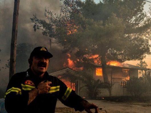 Seorang petugas pemadam kebakaran di Kineta, dekat Athena (AFP)