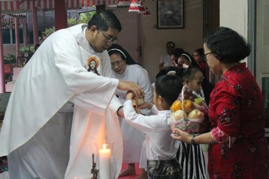 Pastor menerima bahan roti dan anggur serta bahan persembahan yang dibawa seorang anak panti bersama ibu pendamping. (PEN@ Katolik/pcp)