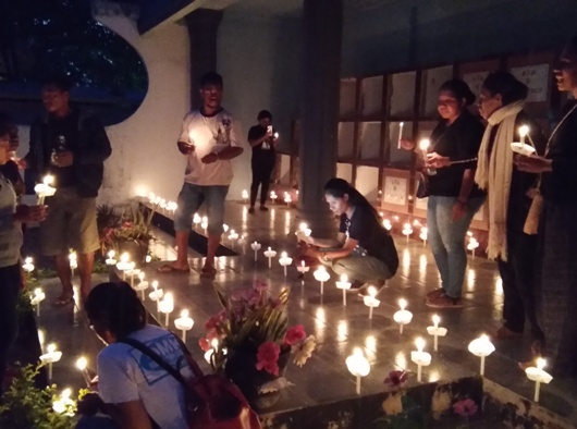 Para peziarah muda  menyalakan 113 lilin untuk para misionaris/ym