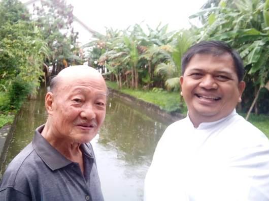 Pastor Patrick (kiri) dan Pastor Pras (kanan) di depan kolam ikan dan kebun pisang di belakang Pastoran Paroki Sungai Raya, Kubu Raya (dok pribadi Pastor Pras)