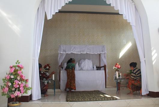 Ibu dari pengurus adat yang khusus ditugaskan membuka bagian khusus Kapela Tuan Meninu merapikan isi 'tabernakel' dan dua ibu lainnya menyalakan lilin-lilin di depannya. PEN@ Katolik/pcp