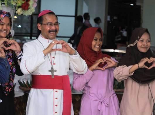 Uskup Agung Semarang Mgr Robertus Rubiyatmoko membuat simbil cinta perdamaian bersama anak-anak muda Muslim. Foto Romo Wito