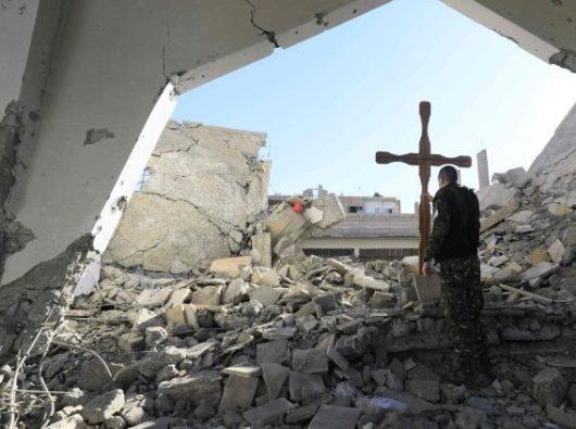 Anggota pasukan Arab-Kurdi Suriah menempatkan salib di reruntuhan, Raqa, Suriah (AFP)