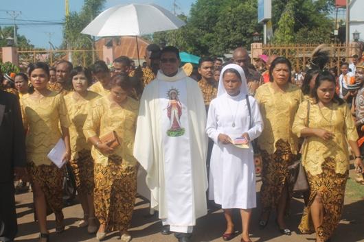 Pastor Emmanuel Ohoiwutun MSC bersama keluarga tiba di halaman gereja. PEN@ Katolik/ym