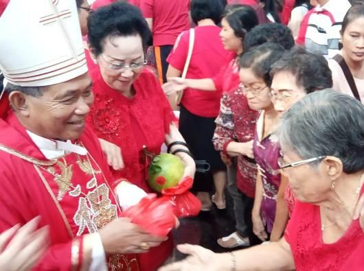 Mgr Agus membagi jeruk dan angpao kepada lansia. PEN@ Katolik/sam