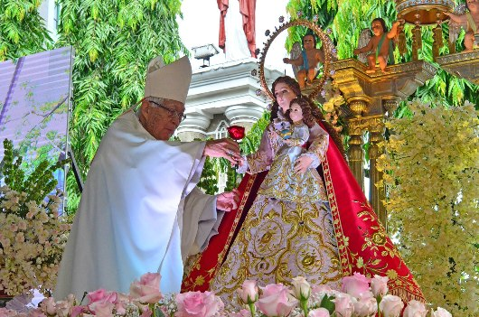 Kardinal Gaudencio Rosales menempatkan mawar merah di tangan kanan Maria. KENNETH RAENEIL FRODOSO