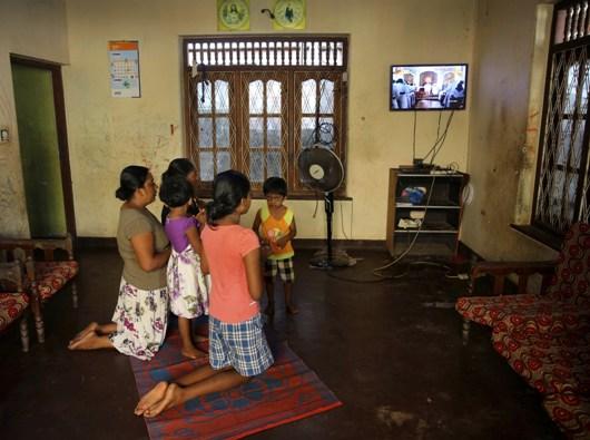 Sebuah keluarga mengikuti Misa di dalam rumah mereka sambil menonton siaran langsung Misa yang dipimpin Uskup Agung Sri Lanka Kardinal Malcolm Ranjith di Negombo, 28 April 2019. Manish Swarup/AP