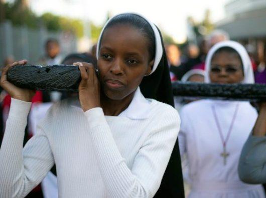 Suster-suster memikul Salib dalam prosesi hening merayakan Jumat Agung di Durban, Afrika Selatan