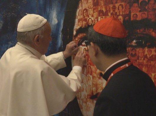 Paus Fransiskus menyisipkan foto orang tua ke dalam foto kolase para migran (Vatican Media)