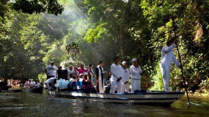 Peziarah Katolik melakukan perjalanan sambil menemani patung Perawan Maria Yang Dikandung Tanpa Noda dalam perarakan sungai yang dilakukan setiap tahun di sepanjang Sungai Caraparu di Santa Izabel do Para