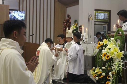 Pastor Aloysius Wahyu Endro Suseno Pr menerima piala berisi anggur dari Mgr Subianto dan membawanya ke altar (PEN@ Katolik/pcp)