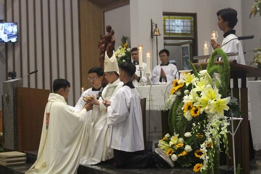 Pastor Valentinus Bayuhadi Ruseno OP menerima piala berisi anggur dari Mgr Subianto dan membawanya ke altar (PEN@ Katolik/pcp)