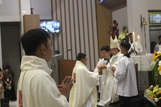 Pastor Yohanes Paulus Subroto Pr menerima piala berisi anggur dari Mgr Subianto dan membawanya ke altar (PEN@ Katolik/pcp)