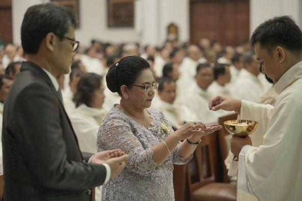 Pastor Valentinus Bayuhadi Ruseno OP memberikan komuni kepada ayah ibunya,  Katharina Endang Suryati dan Bernardinus Budihadi Nursasono