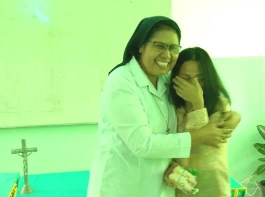 Suster Maria Florentina Memu OSU memeluk seorang staf sekolah yang  mewakili seluruh guru yang terharu dan menangis saat memberikan  cenderamata (PEN@ Katolik/mp)