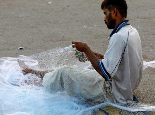 Seorang pria menyiapkan jaring ikan di sepanjang jalan dekat daerah pelabuhan di Karachi, Pakistan