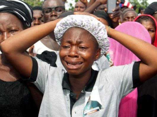 Seorang wanita menangis di pemakaman di Nigeria tanggal 22 Mei 2018, saat 17 umat beriman dan dua imam terbunuh  (AFP)