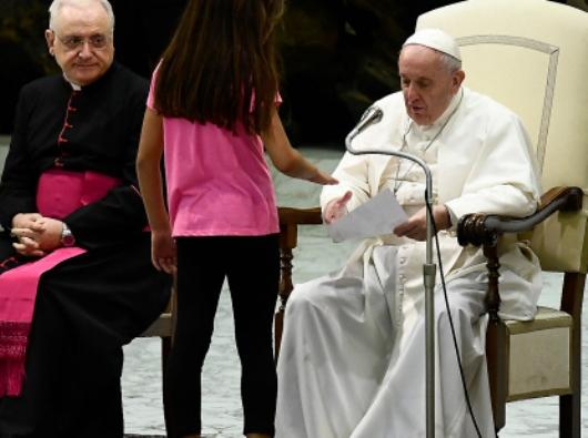 Gadis berkebutuhan khusus datang menyalam tangan Paus Fransiskus, saat Paus memberikan salam dalam berbagai bahasa dalam  audiensi umum.  (Filippo Monteporte/AFP)