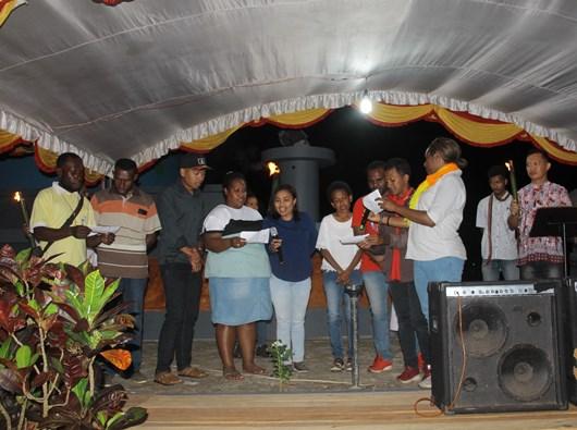 Wakil-wakil OMK KAME membacakan komitmen bersama di tengah anggota OMK KAME yang memegang obor bernyala di depan Patung Hati Kudus Yesus Bandara Mopah (PEN@ Katolik/ym)