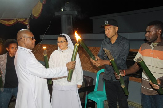 Vikjen KAME Pastor Hengky Kariwop MSC menyalakan api obor salah satu ketua OMK (PEN@ Katolik/ym)