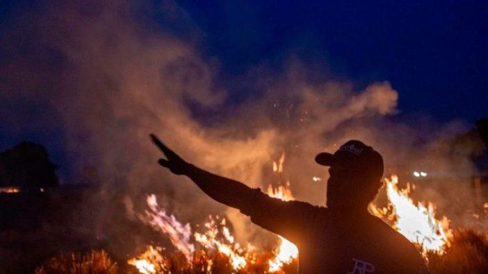 Seorang pekerja memberi tanda saat melihat api menyebar ke pertanian tempat dia bekerja di negara bagian Mato Grosso utara di Brasil. (AFP)