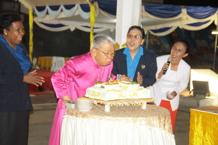 Mgr Mandagi meniup kue ulang tahun  tahbisan uskup (PEN@ Katolik/ym)