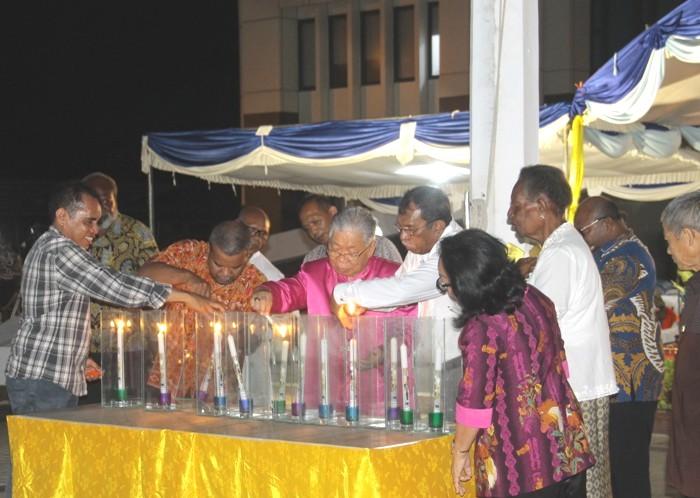 Mgr Petrus Canisius Mandagi MSC bersama Bupati Merauke Frederikus Gebze dan para imam menyalakan lilin sebagai simbol persatuan dan kedamaian (PEN@ Katolik/ym)