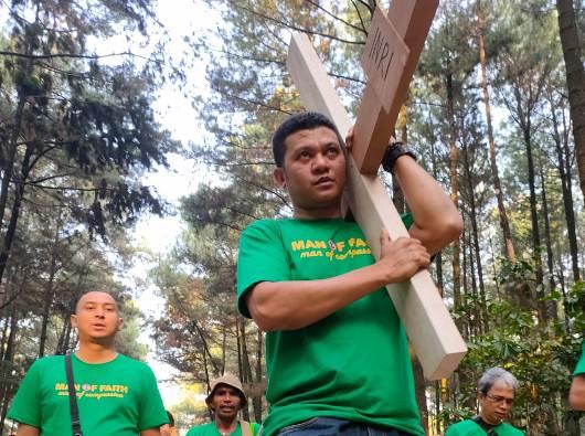 Pastor Herman Yosef Bataona CMF memanggul salib dalam Jalan salib Camping Rohani Komunitas Pria Katolik (KPK) Paroki Santa Helena Curug Tangerang Gunung Pancar Bogor (Foto Dok KPK Curug)