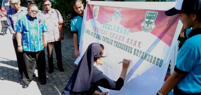 Kepala SMP Katolik Theodorus Kotamobagu Suster Herlina Helena Simanjorang OSU menandatangani deklarasi Sekolah  Ramah Anak (PEN@ Katolik/ampcp)