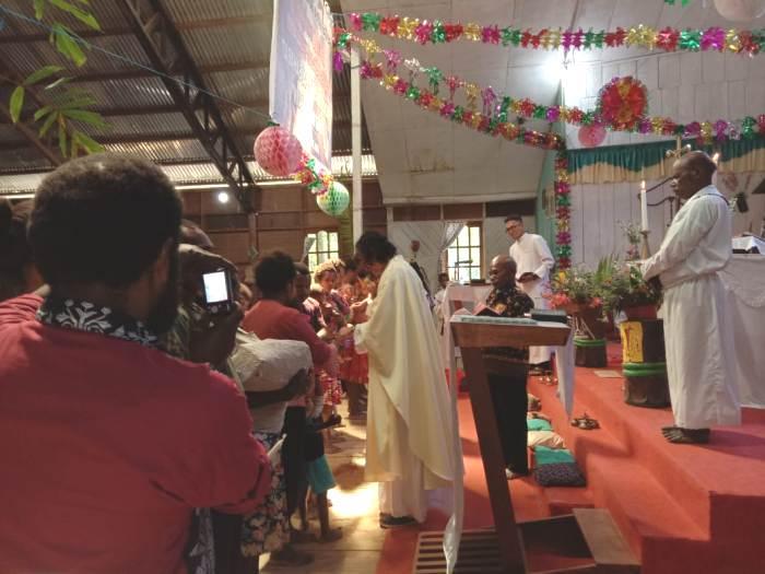 Romo Sudri SJ menerimakan Sakramen Baptis kepada umat dari berbagai stasi (PEN@ Katolik/fr stl)
