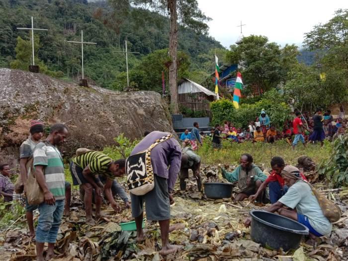 Umat Paroki Modio mengadakan acara Bakar Batu ala tradisional pedalaman Meeuwodidee, Papua, di halaman pastoran (PEN@ Katolik/fr stw)