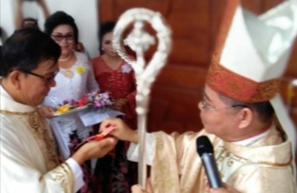 Mgr Rolly memberikan kunci gereja kepada kepala paroki untuk membuka gerbang gereja baru di Maumbi (PEN@ Katolik/af)