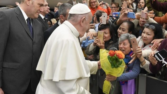 Seorang perempuan memberikan bunga kepada Paus Fransiskus dalam Audiensi Umum   (Vatican Media)
